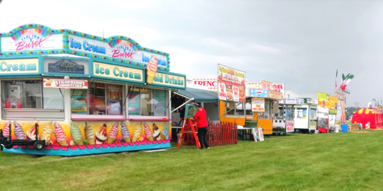 A line of food vendors at a festival.