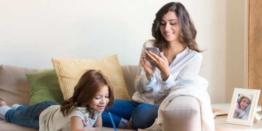 Mom on phone while on couch with daughter