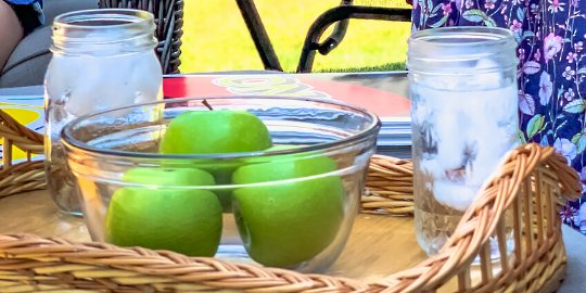 three apples in a bowl with two glasses of ice water on a summer day