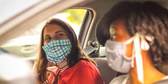 Two masked women in a car wait for their flu vaccines.