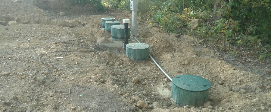 Green septic tanks dug into the dirt.