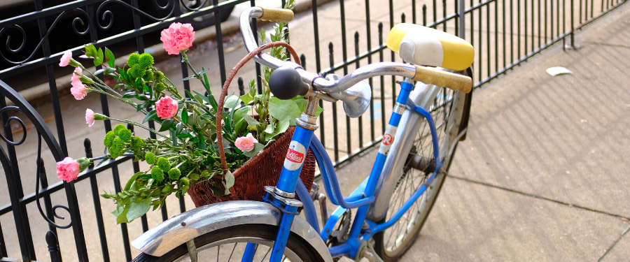 A retro blue bike next to a fence with pink flowers in its basket