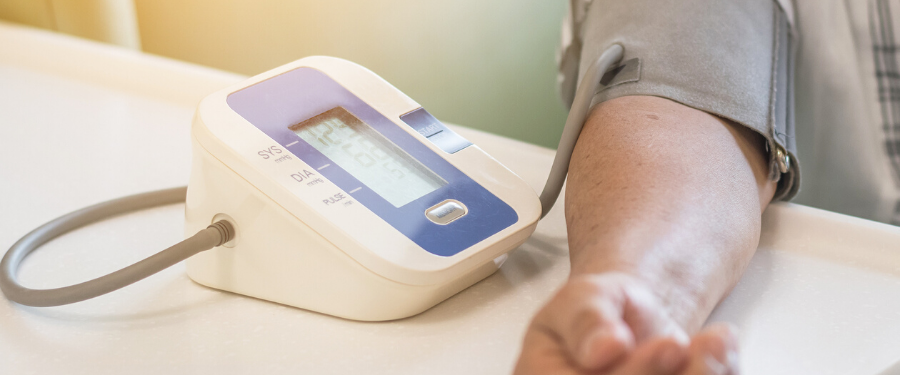 A man's arm in a blood pressure self-monitor machine