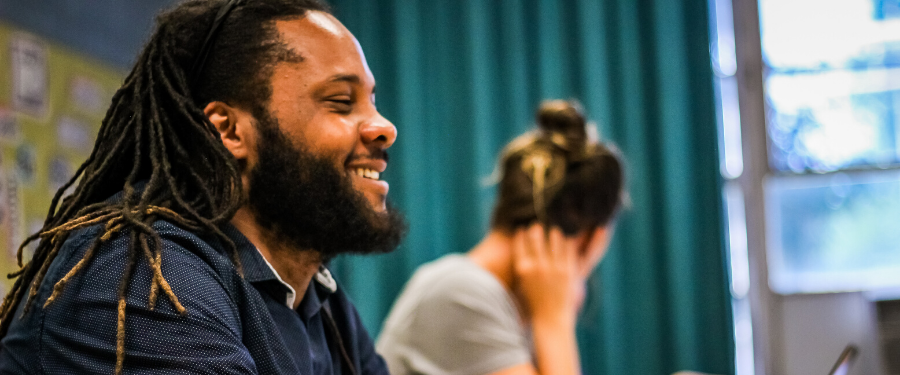 An African American man with dreadlocks smiles in a group meeting.