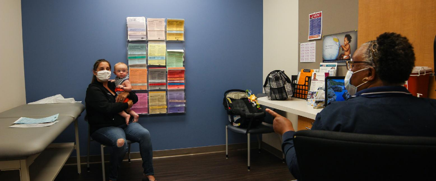 A masked staff member prepares a mom for her baby's vaccine